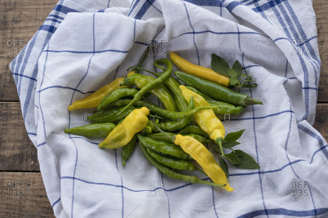 Yellow and green chilies (capsicum)- hot peppers- with leaves on table