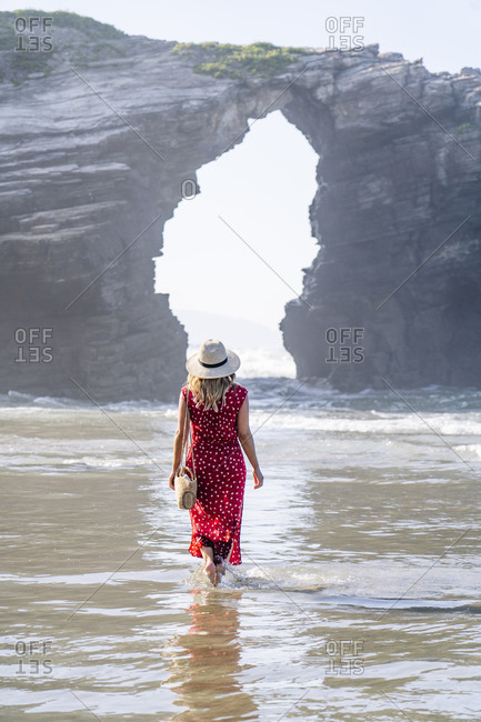 Blond woman wearing red dress and hat and walking along beach- Natural Arch at Playa de Las Catedrales- Spain