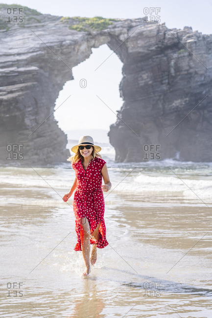 Blond woman wearing red dress and hat and running at the beach- Natural Arch at Playa de Las Catedrales- Spain