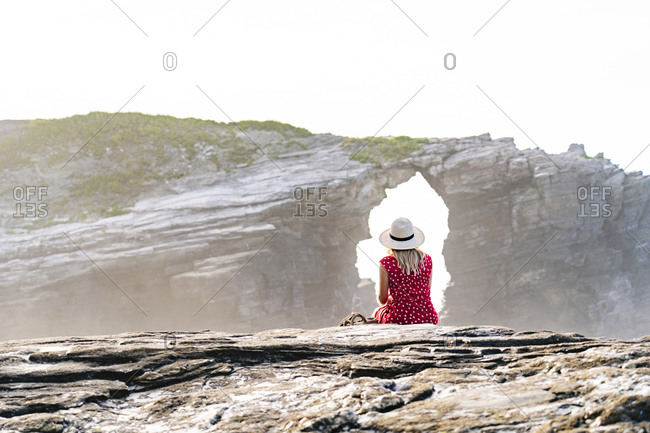 Blond woman wearing red dress and hat sitting on rock and looking to Natural Arch at Playa de Las Catedrales- Spain