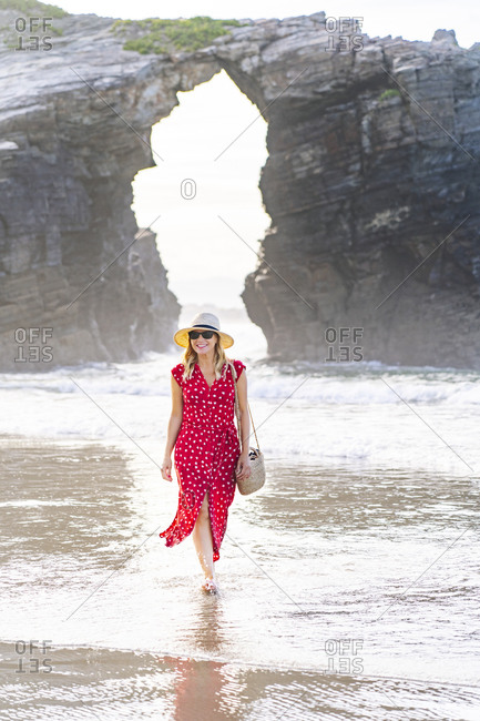 Blond woman wearing red dress and hat and walking at the beach- Natural Arch at Playa de Las Catedrales- Spain