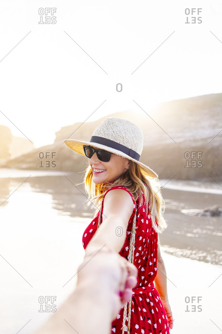 Blond woman wearing red dress and hat and holding hand on the beach- Natural Arch at Playa de Las Catedrales- Spain