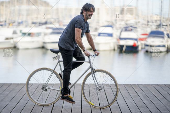 Mature man riding bicycle on boardwalk- Alicante- Spain