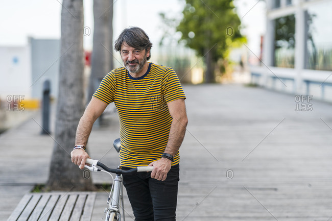 Portrait of smiling mature man with  bicycle- Alicante- Spain