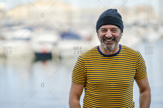 Portrait of laughing mature man wearing cap and striped t-shirt- Alicante- Spain