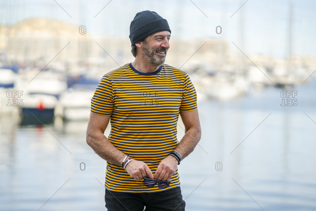 Portrait of smiling mature man wearing cap and striped t-shirt looking at distance- Alicante- Spain