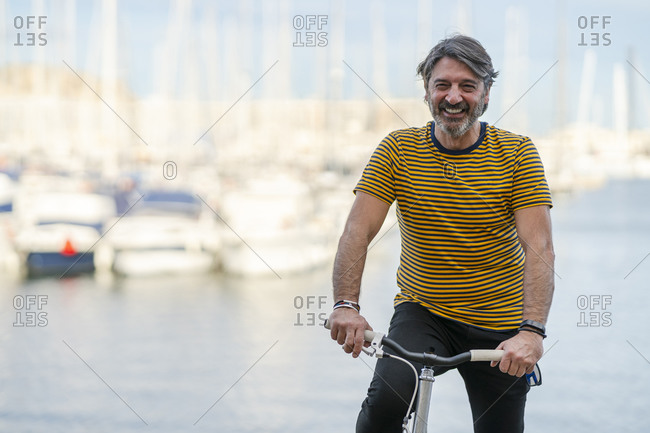 Portrait of laughing mature man  with bicycle in front of harbor- Alicante- Spain