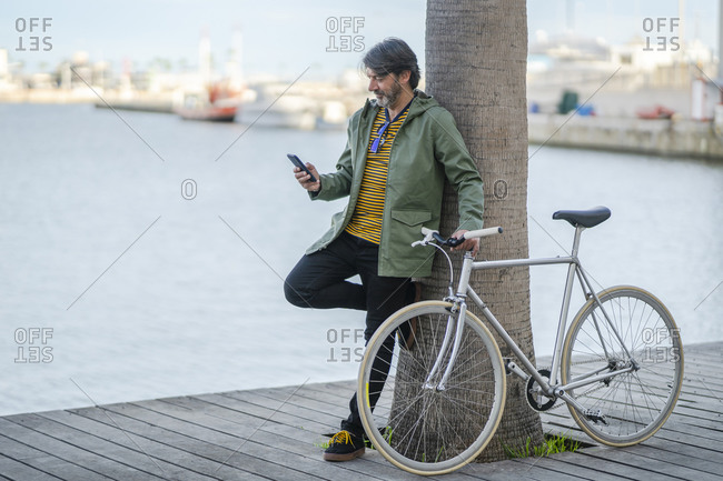 Mature man with fixie bike leaning against palm tree trunk looking at cell phone- Alicante- Spain