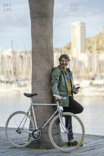 Portrait of relaxed mature man with fixie bike leaning against palm tree trunk- Alicante- Spain