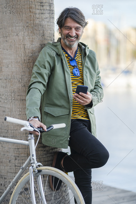 Portrait of laughing mature man with fixie bike leaning against palm tree trunk- Alicante- Spain