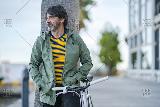 Portrait of serious mature man with  bike leaning against palm tree trunk looking at distance- Alicante- Spain