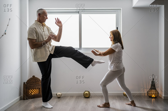 Man and woman practicing martial arts in gym
