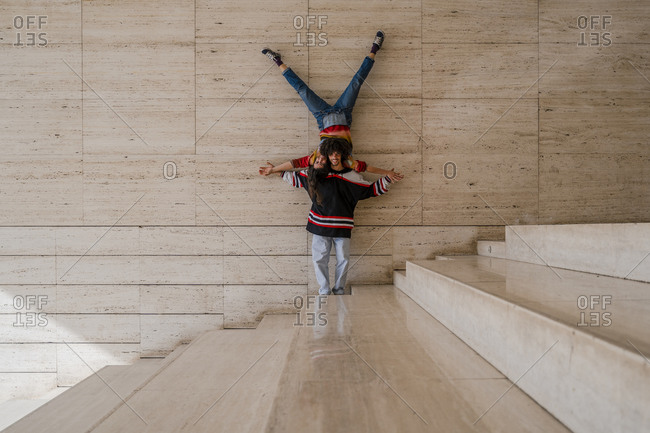 Couple of dancers on a wall- woman balancing upside down on man