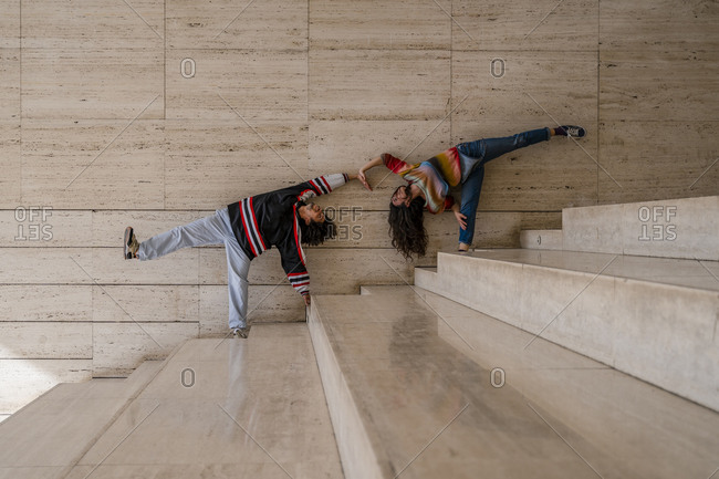Couple of dancers on a wall- lifting the legs