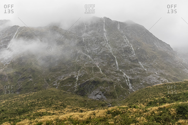 New Zealand- Oceania- South Island- Southland- Fiordland National Park- Continuous rain creating waterfalls on mountainside