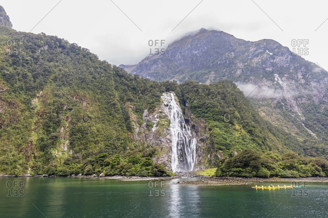 New Zealand- Oceania- South Island- Southland- Fiordland National Park- Port of Milford Sound with Bowen Falls and Barren Peak- Canoeists on water