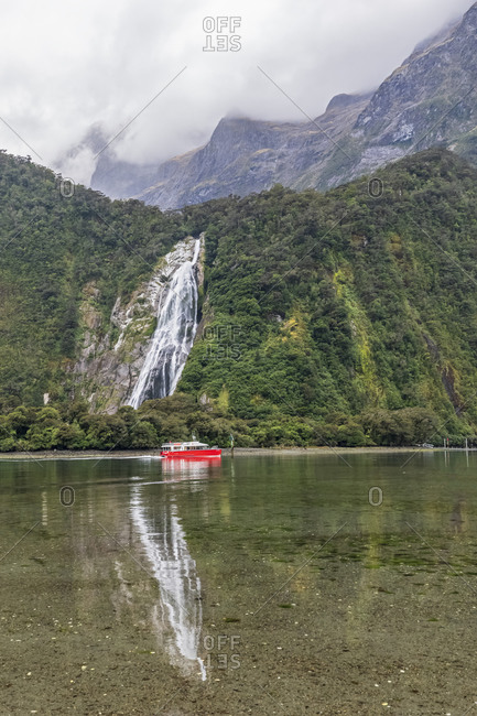 New Zealand- Oceania- South Island- Southland- Fiordland National Park-Waterfall and boat on water