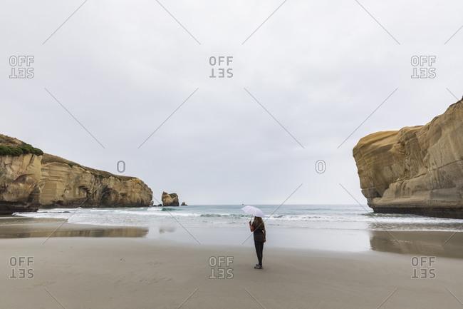New Zealand- Oceania- South Island- Otago- Dunedin- Woman with umbrella on Tunnel Beach