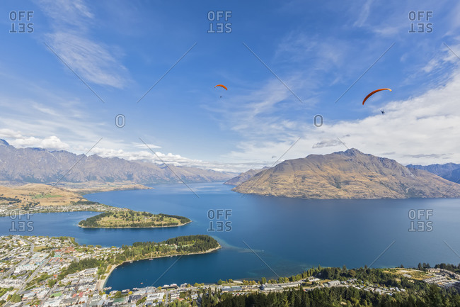 New Zealand- Otago- Queenstown- Paragliders flying over lakeshore town with mountains in background