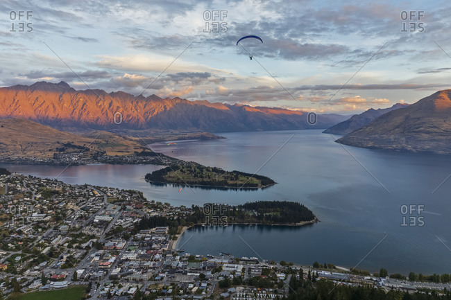 New Zealand- Otago- Queenstown- Paraglider flying over lakeshore town at dusk