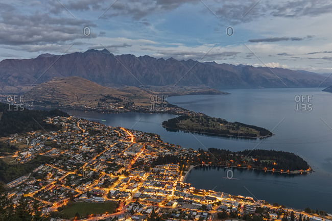 New Zealand- Otago- Queenstown- Town on shore of Lake Wakatipu at dusk with mountains in background