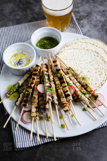 Skewers of meat on plate with yogurt and parsley sauce with flat bread and vegetables