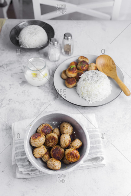 Plate of chicken meatballs with rice and jar with yogurt sauce
