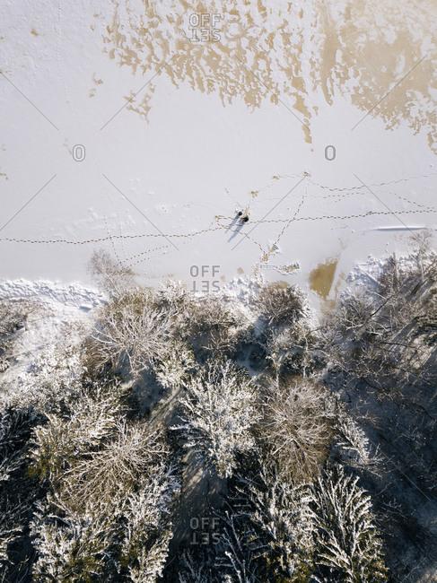 Russia- Leningrad Oblast- Tikhvin- Aerial view of two men fishing on frozen shore