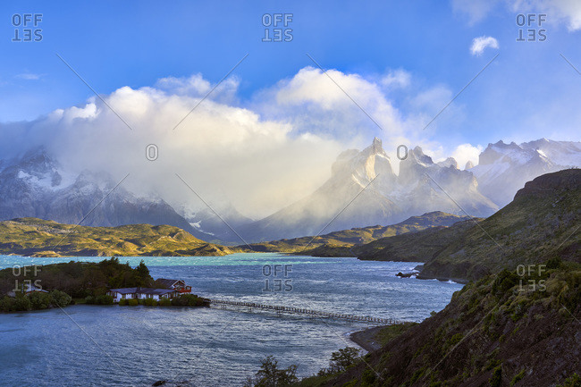 Chile- Ultima Esperanza Province- Lodge on small island of Lake Pehoe with Cuernos del Paine shrouded in clouds in background