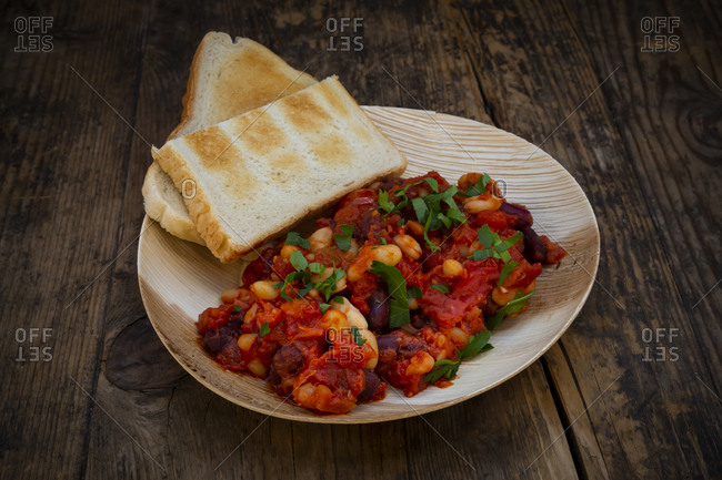 Vegan baked kidney beans- white beans- tomatoes and parsley on environmentally friendly plate made from palm leaves
