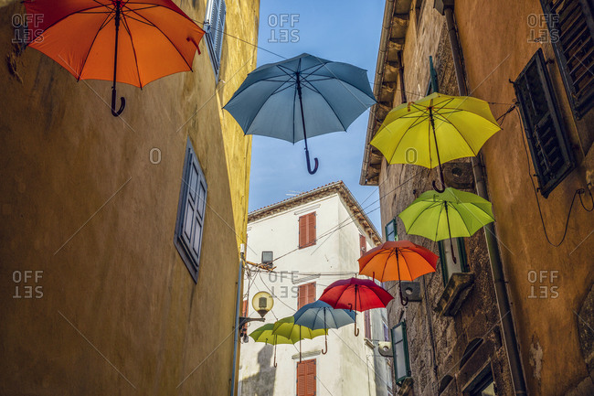 Croatia- Istria- Labin- Low angle view of colorful umbrellas hanging in old town alley