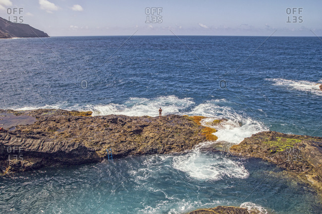 Spain- La Gomera- Hermigua- Man standing on cliff by sea water pool