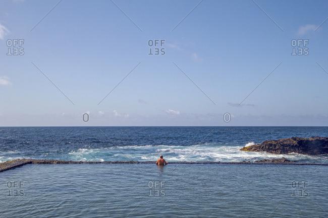 Spain- La Gomera- Hermigua- Man swimming in sea water pool