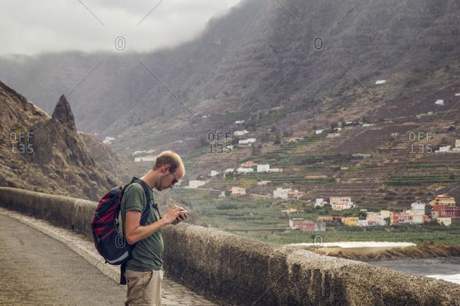 Spain- La Gomera- Hermigua- Young man checking smartphone on the road