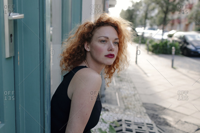 Portrait of red-haired woman in front of a cafe and looking sideways