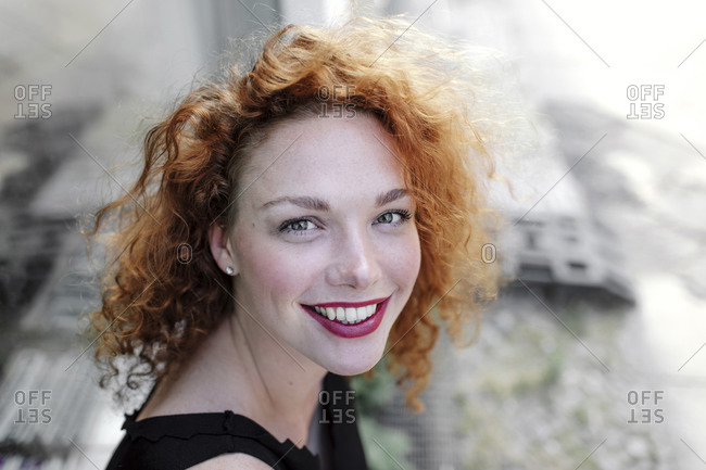 Portrait of smiling red-haired woman looking at camera