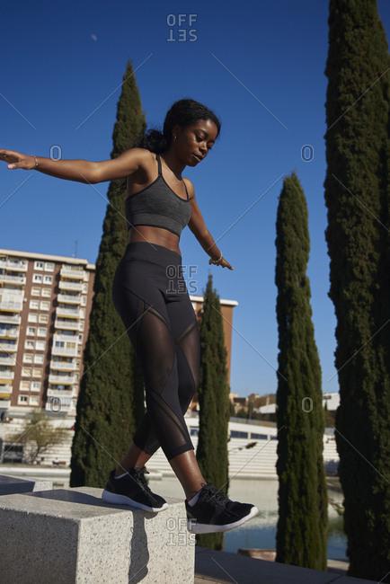 Young sportswoman walking on a stone pillar