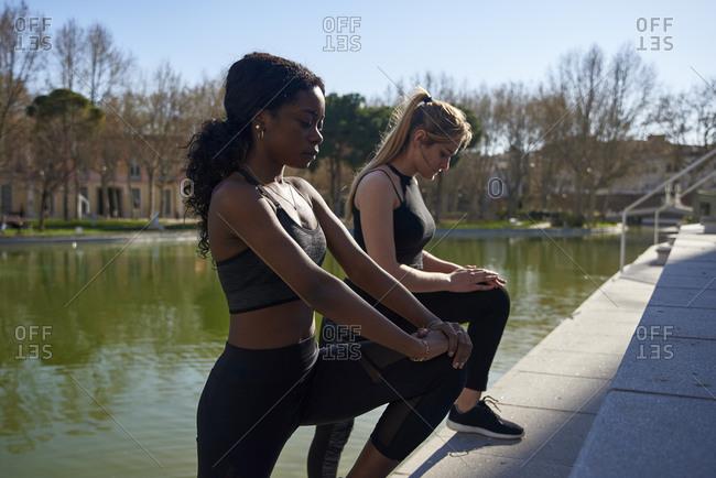 Two sportswomen doing leg stretches