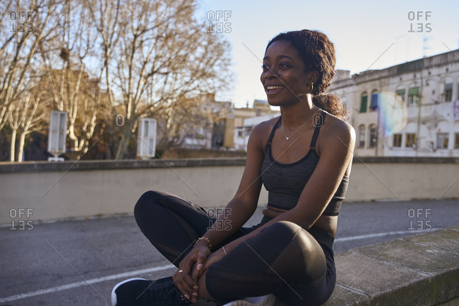 Young smiling sportswoman sitting on a wall