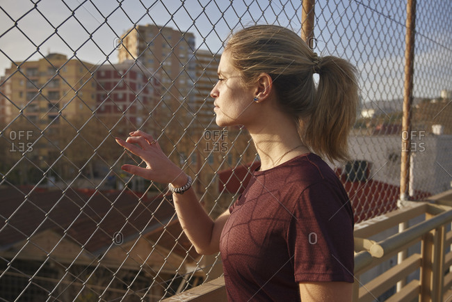 Sporty young woman looking through a fence