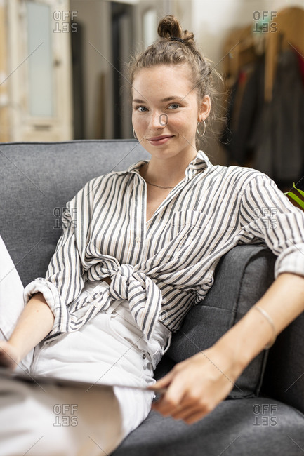 Young woman sitting on couch- holding digital tablet- looking at camera