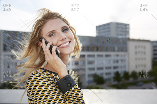 Portrait of happy blond young woman with windblown hair on the phone