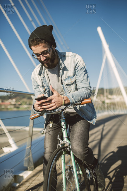Young man commuting in the city with his fixie bike- using smartphone