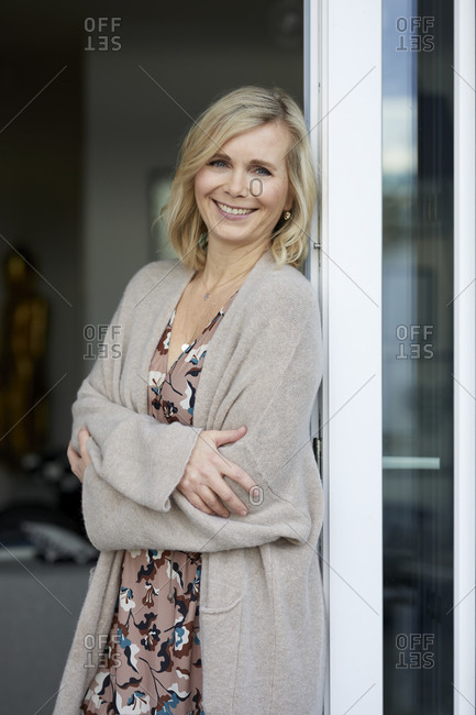 Portrait of smiling blond woman leaning against balcony door at home