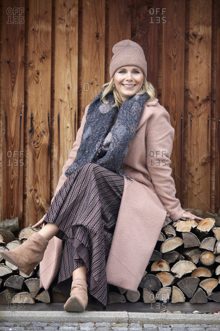 Portrait of smiling woman in winter clothes sitting on stack of wood