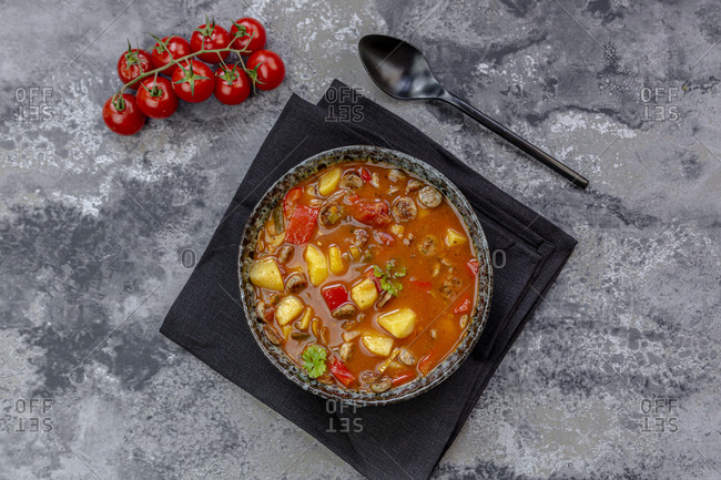 Bowl of sausage goulash with potatoes- tomatoes- bell peppers- leek and parsley