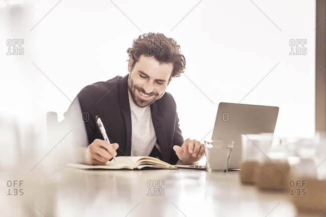 Young man in business jacket working on a laptop and taking notes in a beach house