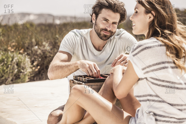 Young couple playing backgammon on terrace