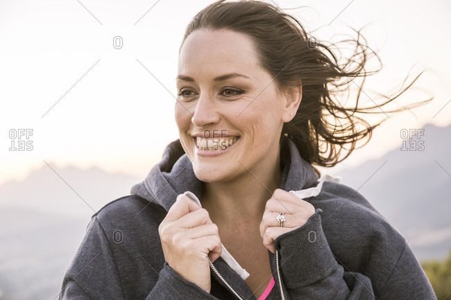 Portrait of happy woman with windblown hair in the countryside