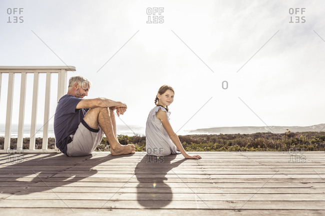 Father and daughter sitting on terrace in sunshine